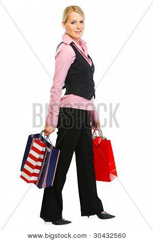 Full Length Portrait Of Smiling Woman With Shopping Bags
