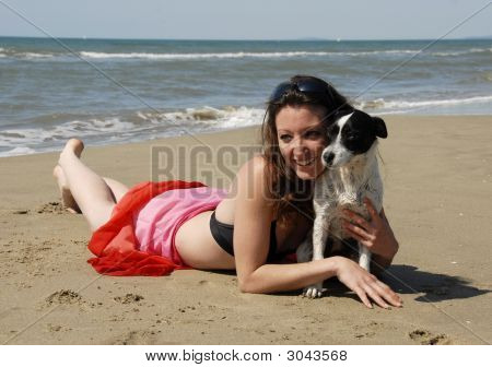 Happy Woman On The Beach With Her Dog
