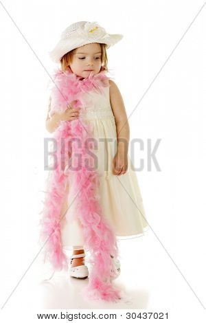 An adorable preschooler dressed totally in white with a feathery pink boa wrapped around her shoulders.  On a white background.