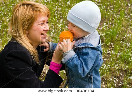 Mum and the son play with an orange on a lawn. They are dared and smile. On a lawn white flowers.