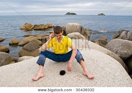 Summer.Sea.The young man speaks by mobile.On a stone the black sea-urchin lays.