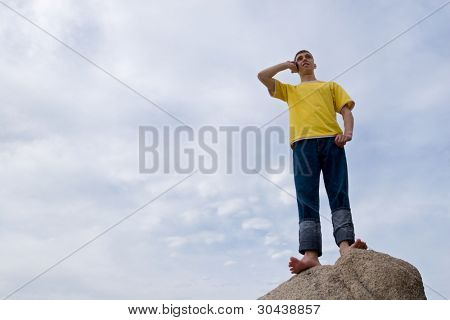 The man stands on a stone and speaks on mobile.