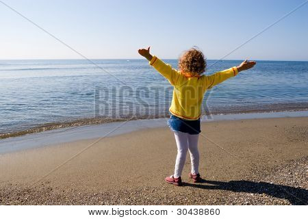 The little girl is admired by sea.