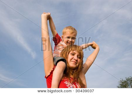 The son sits at mother on shoulders and swings hands, smile.