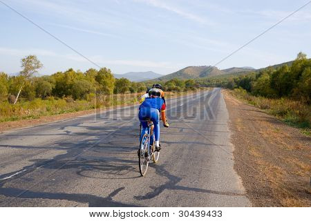 Competitions of young bicyclists.Country road.