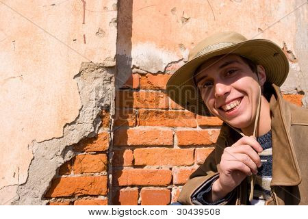 The young man in a hat on a background of an old wall.