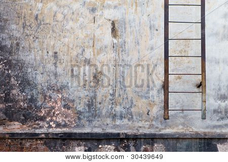 Wall of an old house with a ladder.