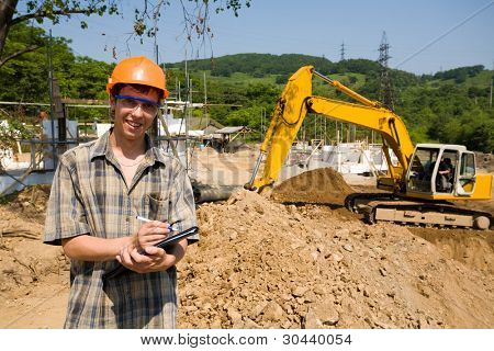 The manager on a working platform.On a background a excavator.