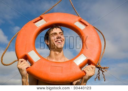 Young (water on a skin) the person poses in a lifebuoy ring.