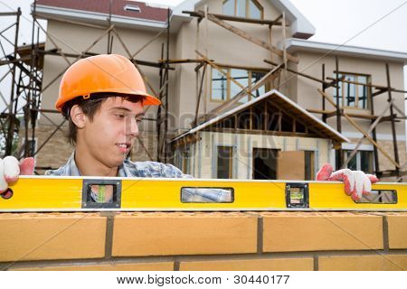 The young builder checks a level of a brick wall.