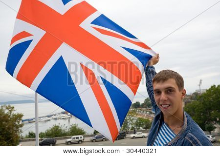 The young man holds in hands the British flag on a background of a sea gulf.