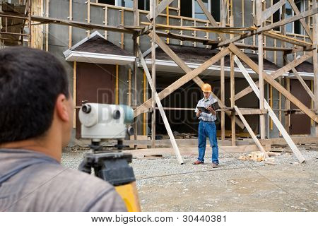 Building site.The builder looks in a level.