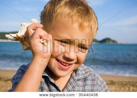 El niño tiene una cáscara en una mano.Costa del mar.