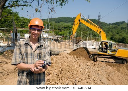 The builder inspector on a working platform.On a background a excavator.