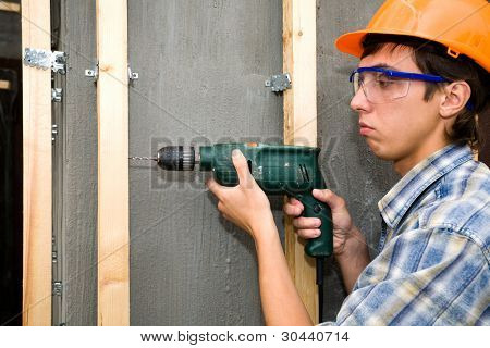 The building worker holds manual drill in hand