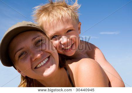 Mãe e a criança (filho), em uma praia em dia de Verão.