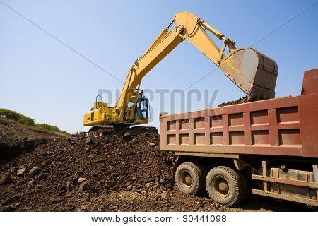 The excavator loads a truck an earthen ground