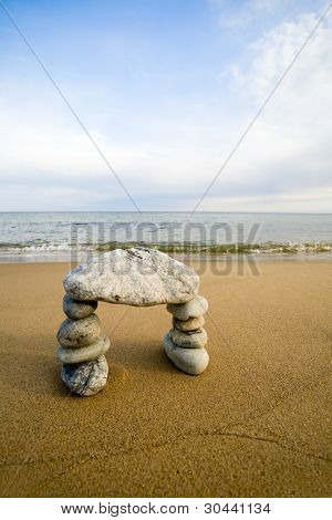 Abstract arch from a natural stones on a background of the sea