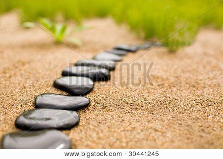 abstrakt Stein Weg auf Sand auf einem Hintergrund von Gras