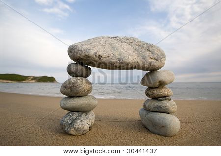 Abstract triumphal arch from a natural stones on a background of the sea