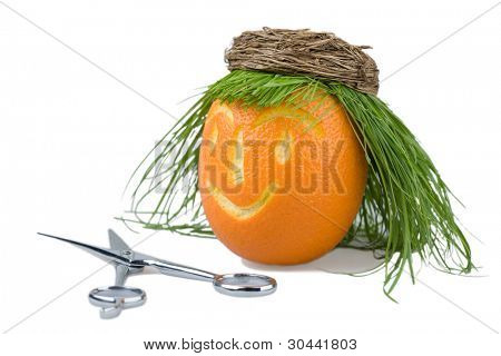 Head of a doll is made of an orange, a natural grass and a wum basket.Abstract hair salon.Scissors.