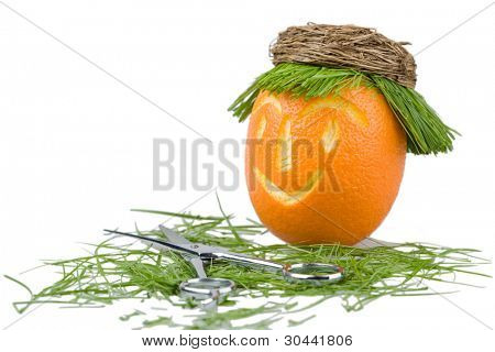Head of a doll is made of an orange, a natural grass and a wum basket.Abstract hair salon.Scissors on a grass.
