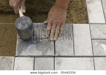 Hands of a manual worker laying concrete paving blocks.