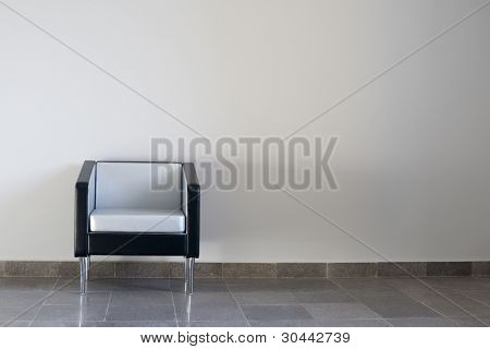 Black-and-silver modern chair on a gray wall