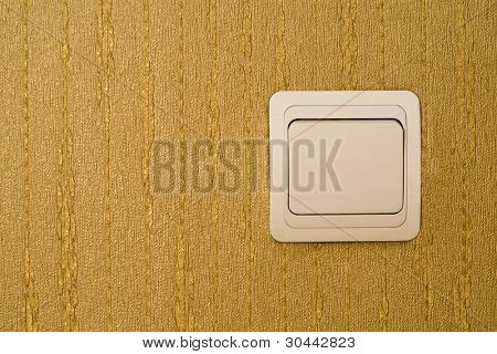 Light switch on a wall with wallpaper of gold color -  place for the text.