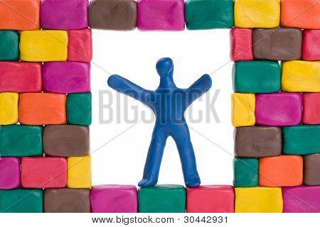 Una plastilina poco albañil construyendo una pared de ladrillos.