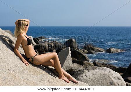 Garota atraente relaxante em uma praia de mar rochoso.