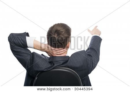 Young businessman sitting in an armchair shows his hand towards the.