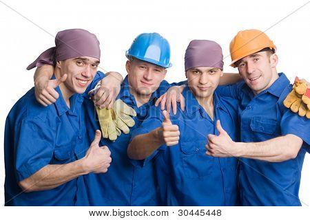 Un amable equipo joven de trabajadores de la construcción muestra los pulgares bien.