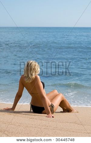 Attractive girl sitting on the sand beside the sea. Sunny day.