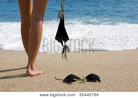Young woman takes off bikini to swiming in the sea.