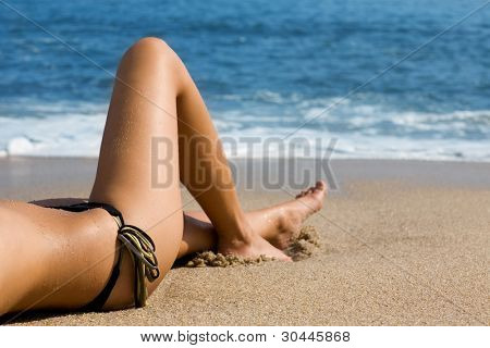Lower half of the girl body lying on the beach by the sea.