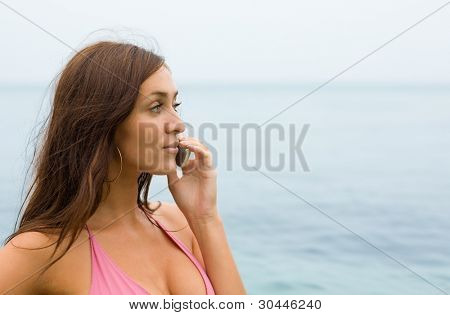 Attractive girl talking on a cell phone on the beach.