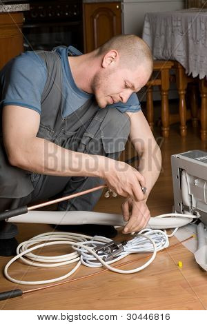 Air conditioning technician prepares a new air conditioner to be installed in the apartment.