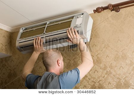 Air conditioning technician installs a new air conditioner in the apartment.