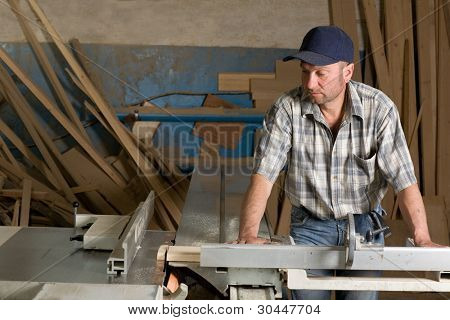 Carpenter working on woodworking machines in carpentry shop.