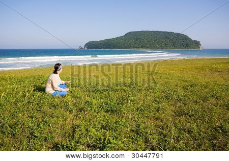 Woman looks at the Petrova island. Japanese sea. State Nature Reserve Lazovskiy. Primorsky Kray. Russia.