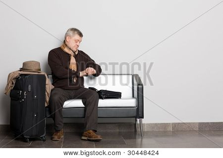 Middle aged man looking at his watch. Waiting hall.