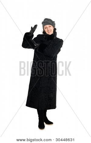 Smiling woman in a fur coat from broadtail (karakul, astrakhan, lambskin).