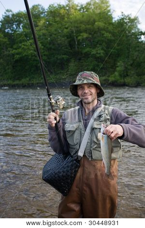 Happy fisherman holds salmon(char). Morning.