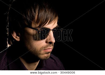 Young man with a stylish haircut in sunglasses