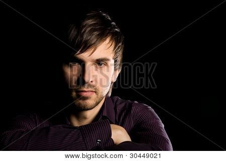 Handsome young man with a serious look on a black background.