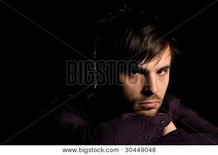 Portrait of serious young man on a black background