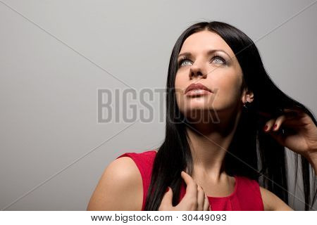 Beautiful young woman surprised looking up against the gray walls