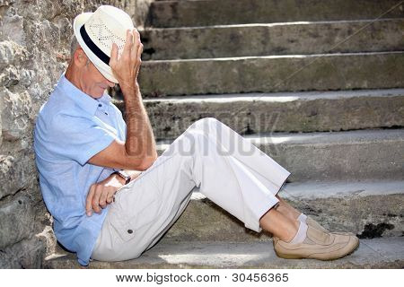 Senior man sitting on some stone steps
