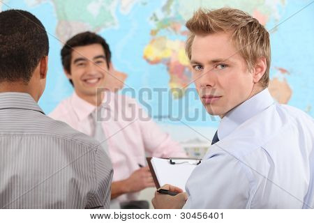 Young businessman holding a clipboard during a meeting